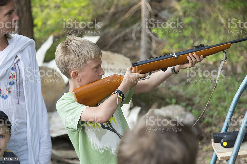 Young boy shooting with air rifle. stock photo