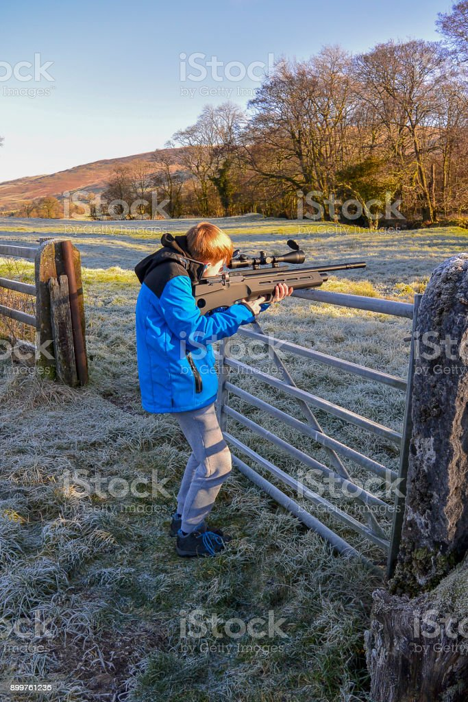 Young boy shooting with air rifle (portrait) stock photo