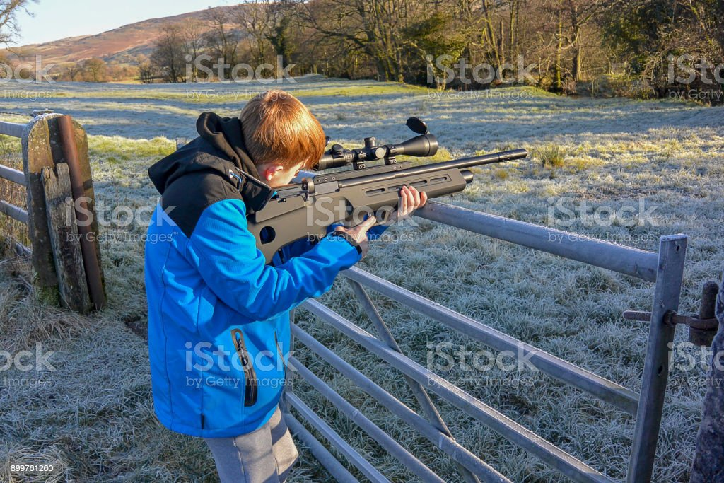 Young boy shooting with air rifle (landscape) stock photo