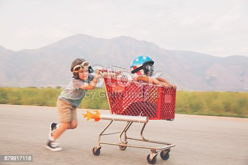 Two young boys wearing racing helmets and racing goggles stand on a rural street for some racing. One is sitting in a shopping cart with rockets strapped on the side. They are looking at the camera excited for the upcoming race. Image taken in Utah, USA.
