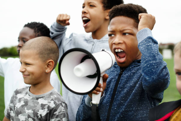 young boy shouting on a megaphone in a protest - protestor stock pictures, royalty-free photos & images