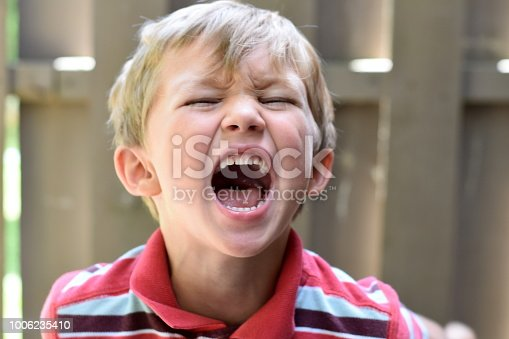 Young boy tilts head back expressing anger