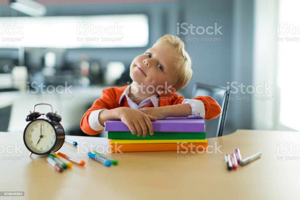 Young boy sit at the desk in the office royalty-free stock photo