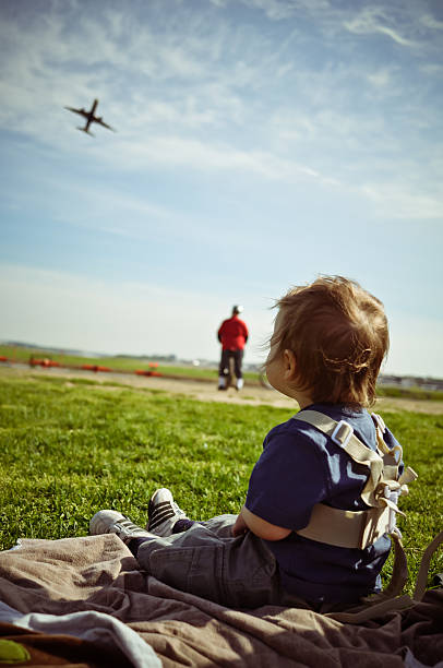Young Boy Sits And Watches Planes Take Off  ronald reagan washington national airport stock pictures, royalty-free photos & images