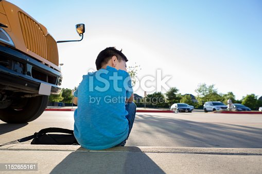 1031397608 istock photo Young boy sits on curb after a hard school day 1152655161