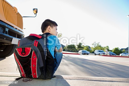 Since he is not riding the bus that day, a young boy waits by the school bus for his dad to come pick him up.