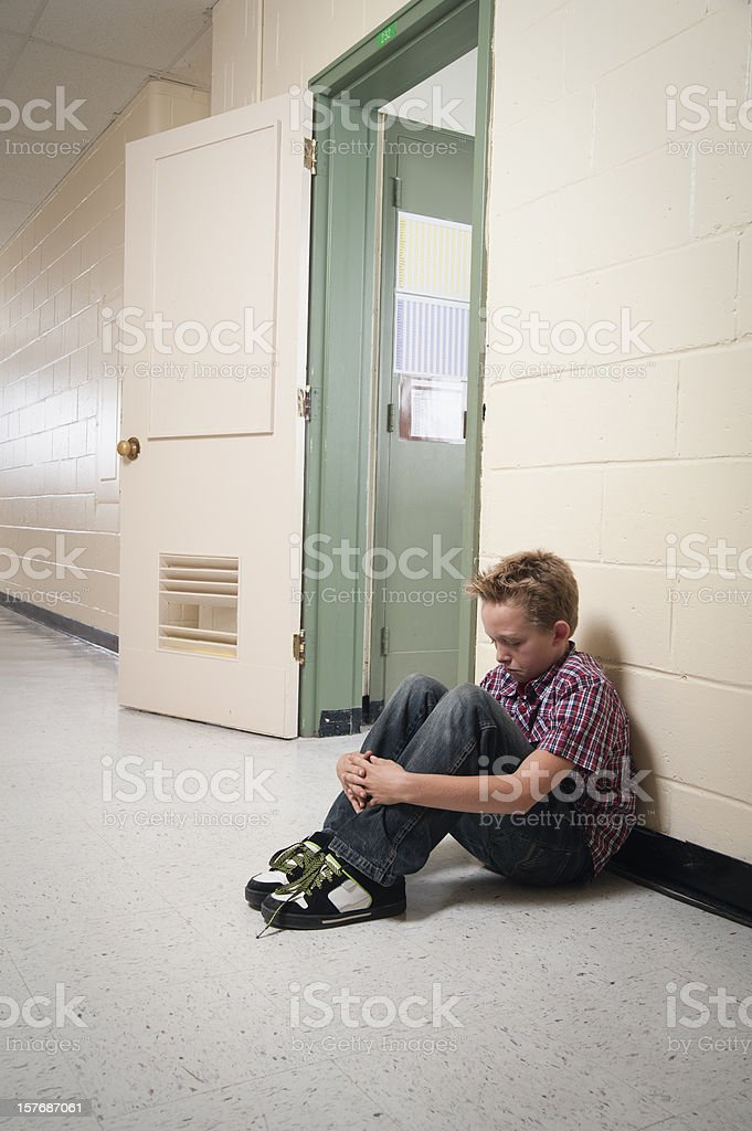Young boy sitting alone out of classroom. stock photo