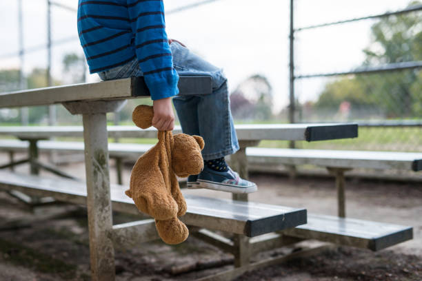 Young boy sitting by himself on on bleachers. stock photo