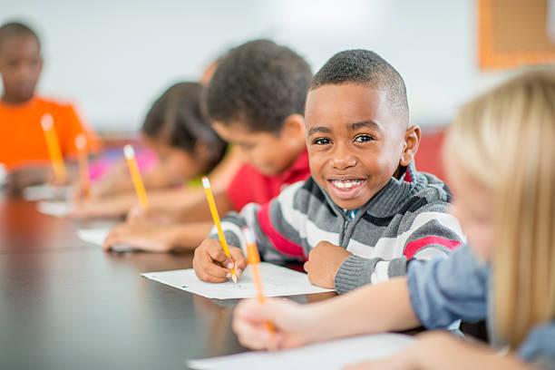 jovem garoto sentado felizes em sala de aula - aula de redação - fotografias e filmes do acervo