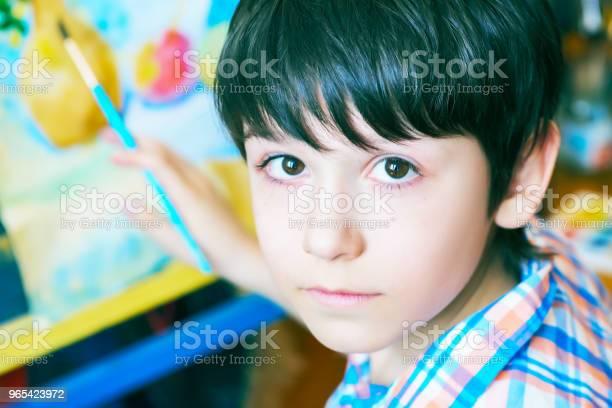 Foto de Jovem Rapaz Sentado Em Frente Ao Cavalete Pintura Um Peixe Segurando Um Pincel Na Mão Menino Está Se Preparando Para Se Tornar Um Artista e mais fotos de stock de Arte