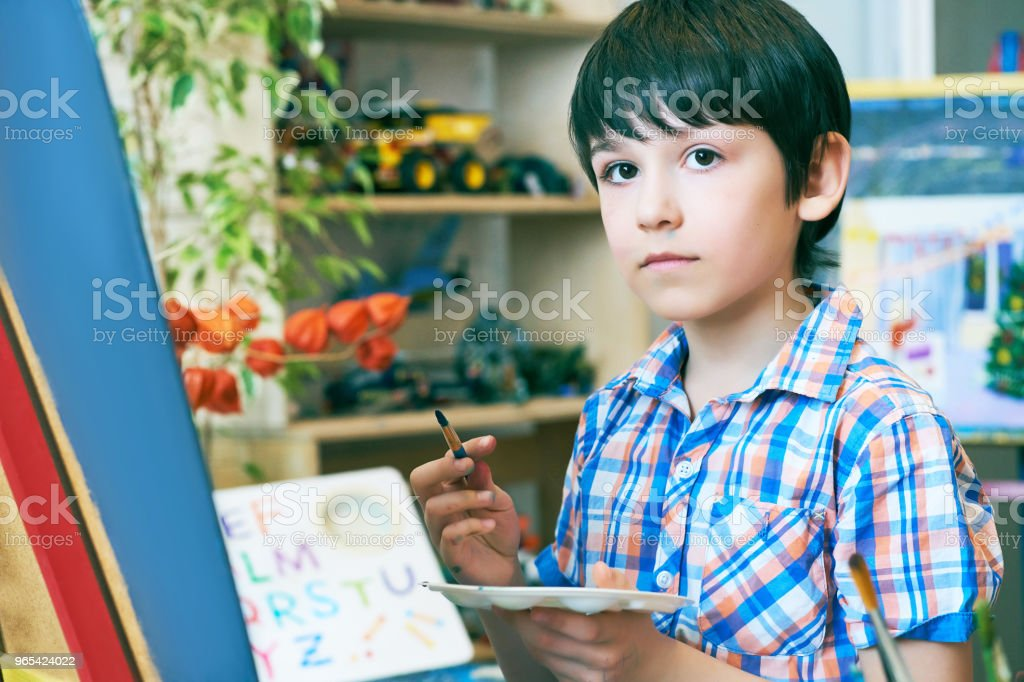 Young boy sitting in front of easel painting a fish, holding a brush in hand. Boy is getting ready to become an artist royalty-free stock photo