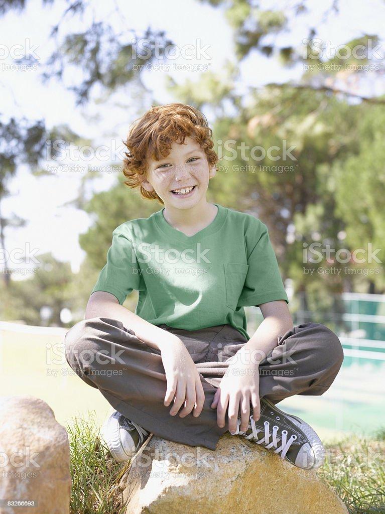 Young boy sentada en el parque foto de stock libre de derechos