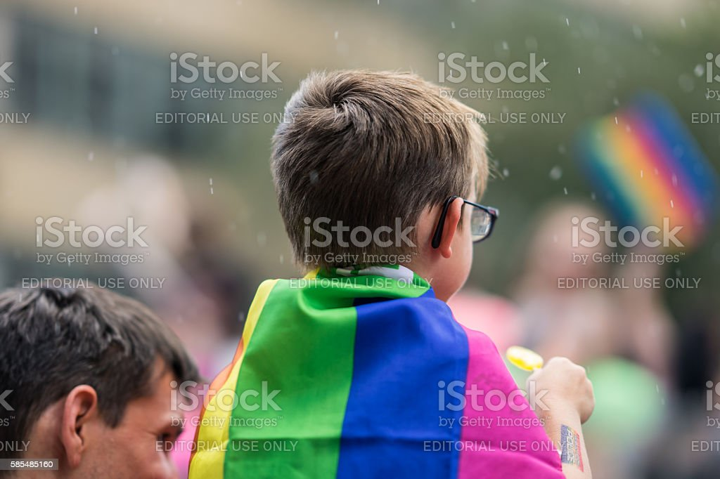 Young boy sitting on dad's shoulders in a crowd. stock photo
