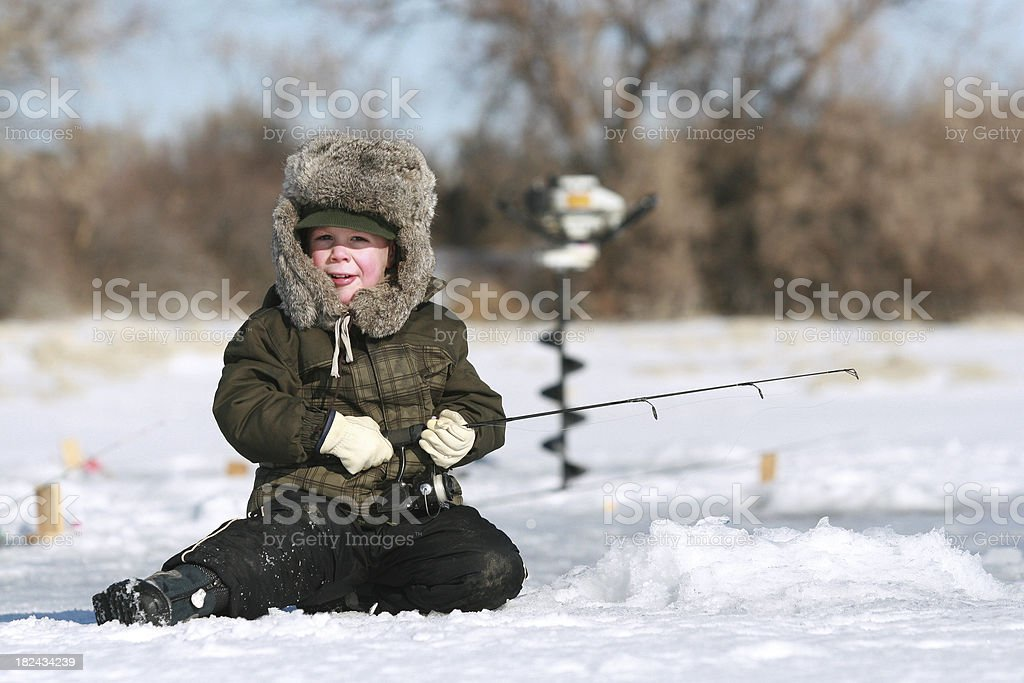 Young boy sitting on snow ice fishing  stock photo