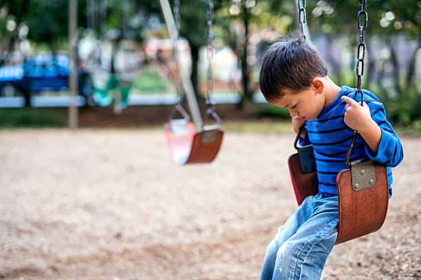 Young boy sitting on swings alone looking sad stock photo
