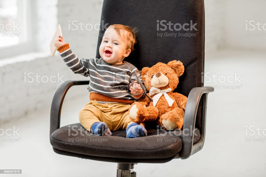Young boy sitting on the office chair stock photo