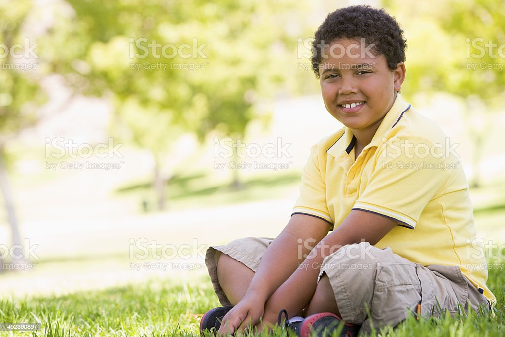 Young boy sitting outdoors smiling royalty-free stock photo