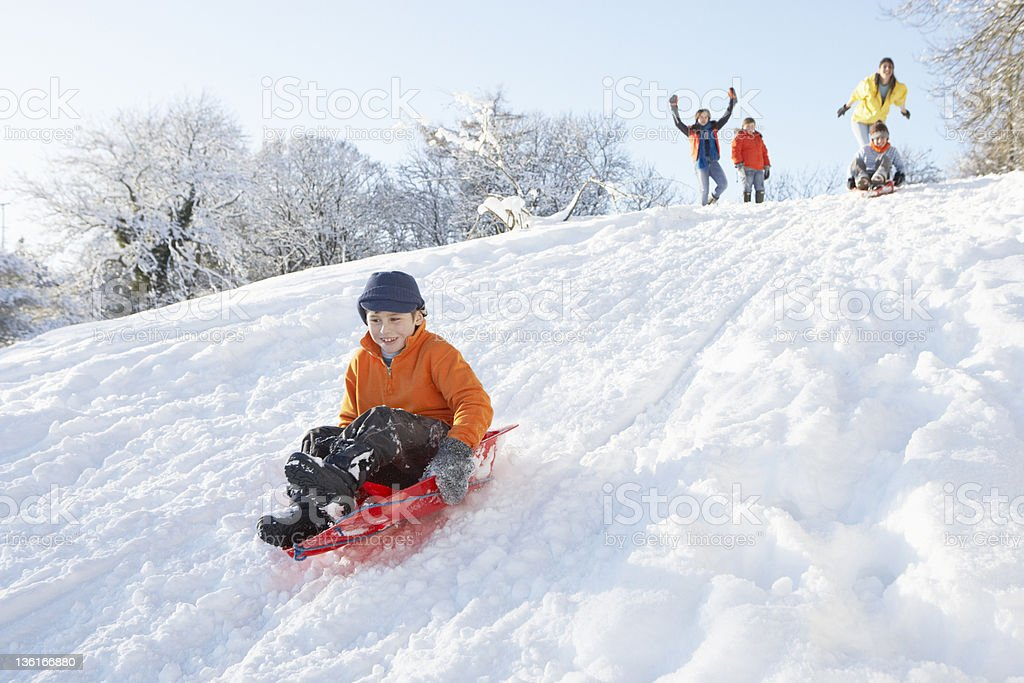 Young Boy Sledging Down Hill With Family Watching stock photo
