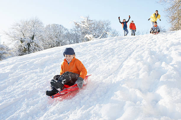Junge Sledging Down Hill mit Familie Watching – Foto