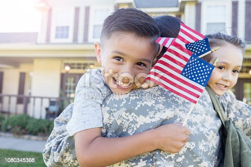 Young, Hispanic boy smiles as he holds a flag in each hand and smiles. He and his sister hug his mother in uniform who has just arrived home.