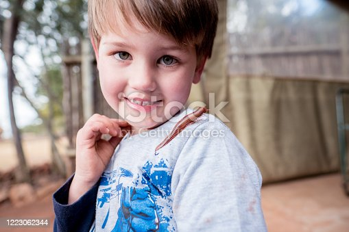 A young boy smiles at centipede crawls on his shoulder, insect