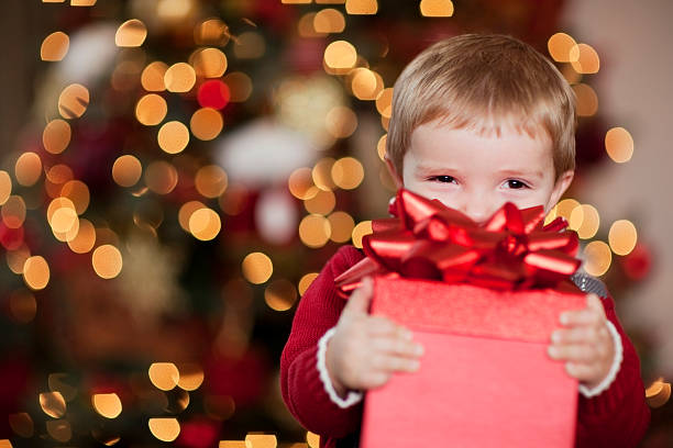 giovane ragazzo smiles con il suo regalo di natale - regalo natale foto e immagini stock
