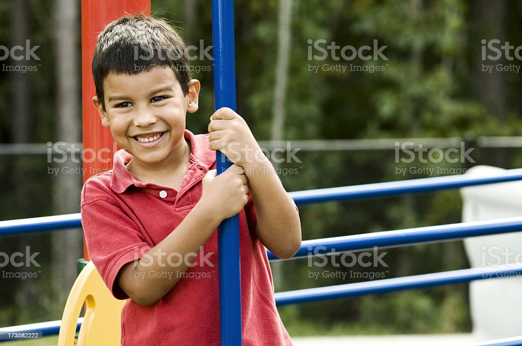 Young boy smiling at a playground royalty-free stock photo