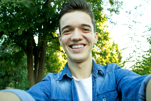 istock Young boy smiling at the park is taking selfie. 1069315552