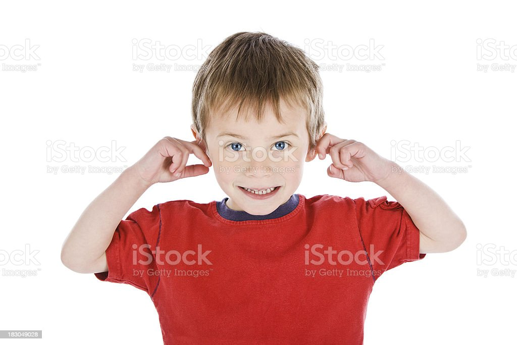 Young boy smiling with finger in his ears on white stock photo