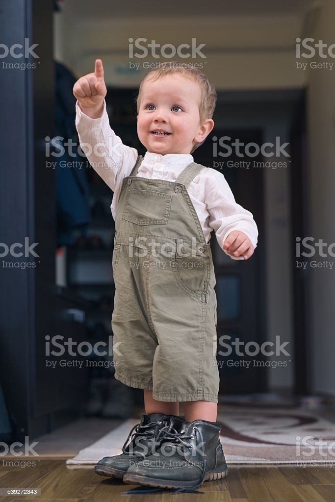 Young boy standing in his father's shoes and pointing up stock photo