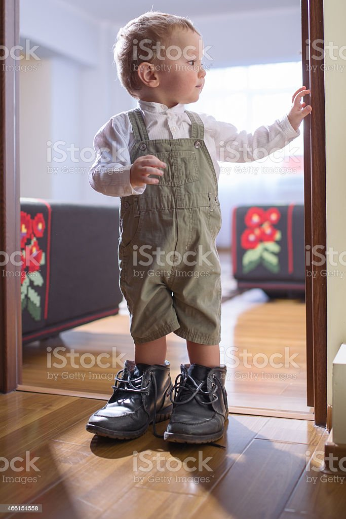 Young boy standing in his father's shoes by the doorway stock photo