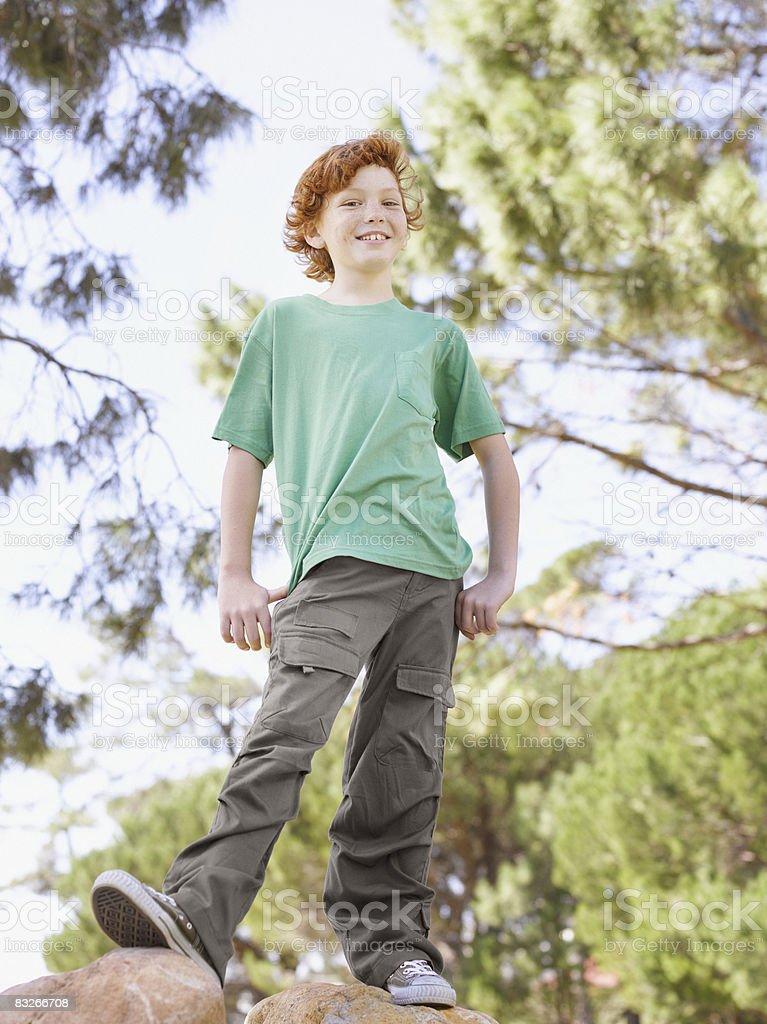 Młody chłopiec stojący na kamienie w parku zbiór zdjęć royalty-free