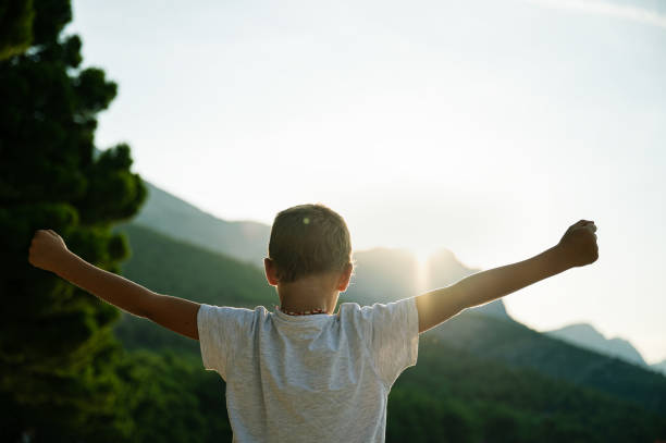 Young boy standing outside at sunrise stock photo