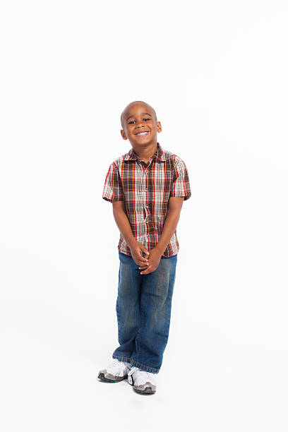 Young boy standing with a cute smile isolated on white stock photo