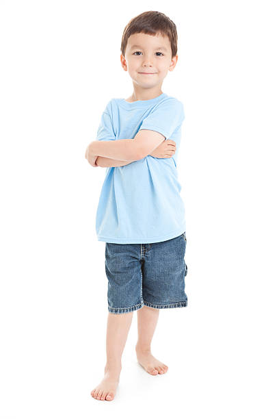 Young Boy Standing With Arms Crossed, White Background stock photo
