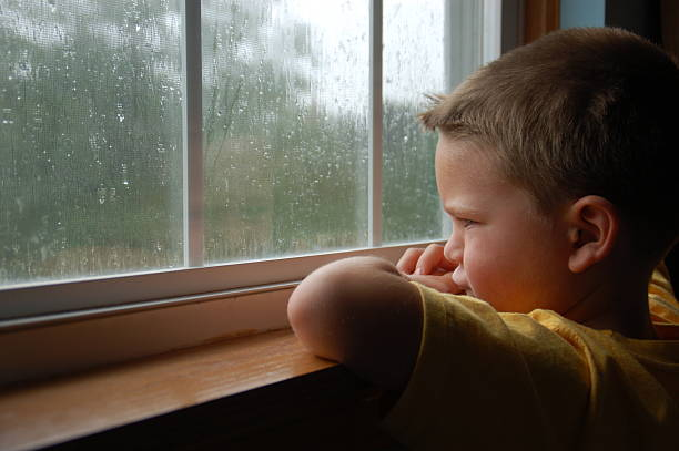 young boy staring out a window as it rains - boy looking out window stock pictures, royalty-free photos & images