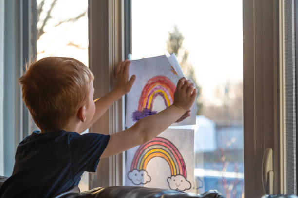 Young Boy sticking his drawing on home window during the Covid-19 crisis at sunset stock photo