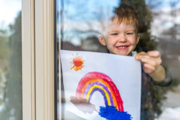 młody chłopiec przyklejając swój rysunek na oknie domu podczas kryzysu covid-19 - nadzieja zdjęcia i obrazy z banku zdjęć