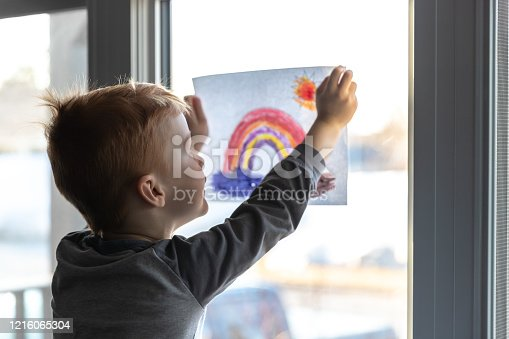 Young Boy sticking his drawing on home window during the Coronavirus Covid-19 crisis, view from inside the house. Many people are putting a rainbow to tell neighbours that people inside this house are ok. #Stayathome #cavabienaller