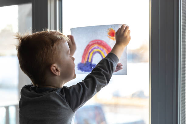 Young Boy sticking his drawing on home window during the Covid-19 crisis Young Boy sticking his drawing on home window during the Coronavirus Covid-19 crisis, view from inside the house. Many people are putting a rainbow to tell neighbours that people inside this house are ok. #Stayathome #cavabienaller flatten the curve stock pictures, royalty-free photos & images