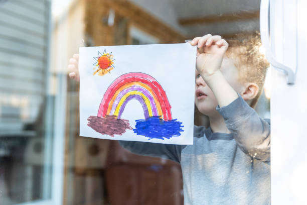 Young Boy sticking his drawing on home window during the Covid-19 crisis stock photo
