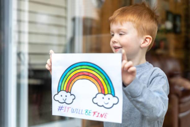 Junge Kleben seine Zeichnung auf Hausfenster während der Covid-19-Krise – Foto