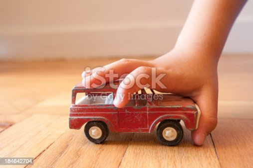 184659330 istock photo Young boy stopping a toy SUV in its tracks 184642704