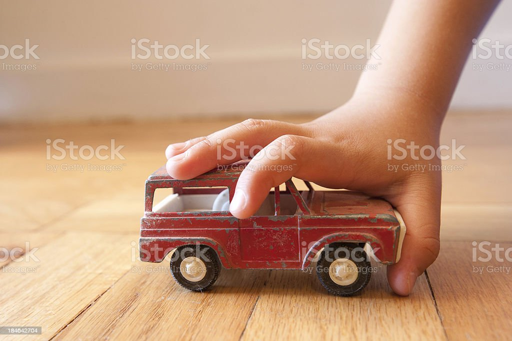 Young boy stopping a toy SUV in its tracks stock photo