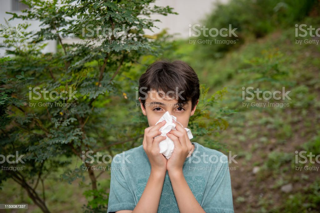 Young boy is outdoors in nature and is figthing his seasonal...