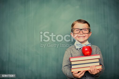 A young and vintage student is ready to learn at school. First, he will give his teacher an apple.