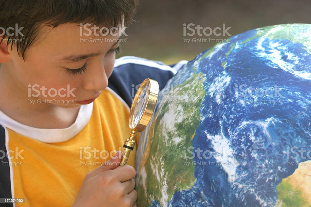 Young boy studying a globe with a magnifying glass royalty-free stock photo