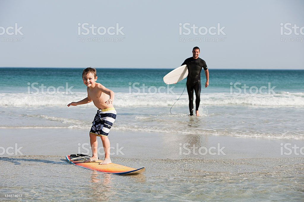Young boy surf en agua superficiales - foto de stock
