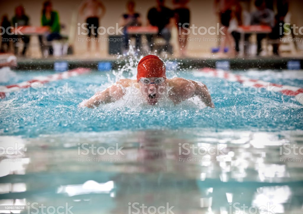 Young man swimming butterfly stroke for high school varsity sports.