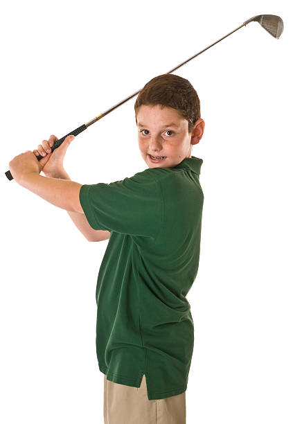 Young boy swinging a golf club stock photo